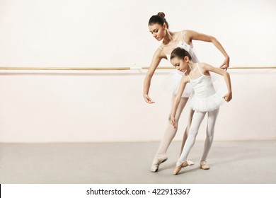 Little ballerina dancing with ballet teacher in dance studio