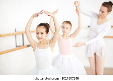Little ballerina dancing with her arms over head while teacher helping her friend near by