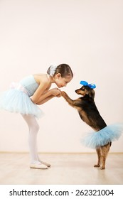 Little ballerina dancing with her cute dog in dance studio. They both wearing a tutu