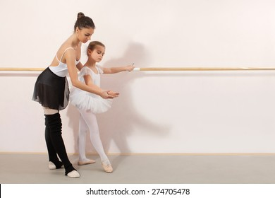 Little ballerina dancing with personal ballet teacher in dance studio. Teacher helping little ballerina and they using stick on the wall