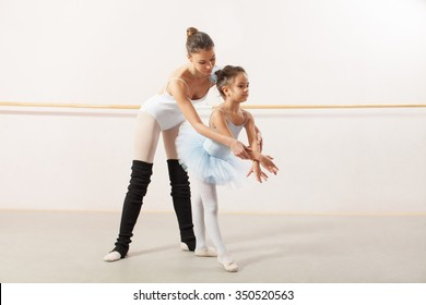 Little ballerina dancing with personal ballet teacher in dance studio. Teacher helping little ballerina to make a right elegant move