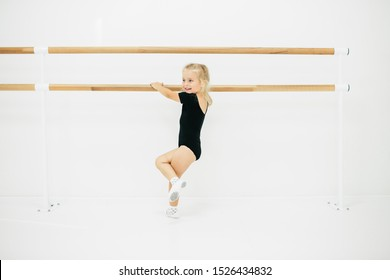 Little ballerina girl in black. Adorable child dancing classical ballet in a white studio. Children dance. Kids performing. Young gifted dancer in a class. Preschool kid taking art lessons.