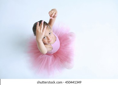 Little ballerina girl in a pink tutu sit on floor. Cute Preschool child dancing classical ballet in white studio. Young graceful dancer in class looking at camera with smile and tender emotion