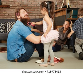 Little ballerina girl playing with father at home.