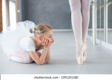 Little ballerina is looking at professional ballet dancer. Cute kid girl dreaming of growing up. Adult dancing legs in ballet pointe shoes. Concept of classical dance school, practicing for children.