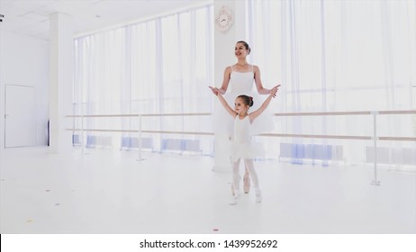 Little ballerina on personal ballet lesson in dance class. Ballet teacher with girl in tutu are training steps synchronously and simultaneously. They are on tiptoe in pointes holding hands.