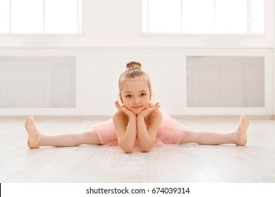 Little ballerina in split on floor, copy space. Smiling baby girl dreaming to become professional ballet dancer, classical dance school
