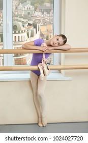 Little ballerina in studio on city background. Cute little girl holding ballet shoes in ballet class. Ballet girl in purple leotard.