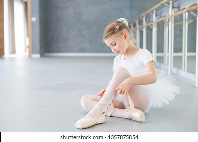 Little ballerina is trying on pointe shoes in ballet class. Cute kid girl is sitting on floor under barre. Child is wearing in white ballet clothes and dress with tutu skirt.