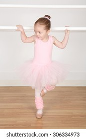 Little ballerina wearing a tutu dancing at the barre