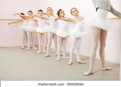 Little ballerinas dancing with ballet teacher in dance studio. Teacher doing exercise, and little ballerinas is watching and following her movements while using stick on the wall