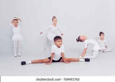 Little ballerinas girls and boy doing splits on white floor, copy space. Smiling babies dreaming to become professional dancerd, classical dance school