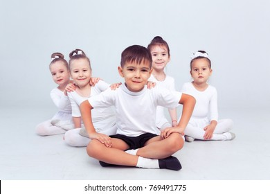 Little ballerinas and kid ballerun doing exercises and sitting on floor in white ballet class.