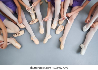 Little ballerinas putting on shoes, cropped image. Group of teen ballerinas sitting on the floor and adjusting their pointe shoes, top view.