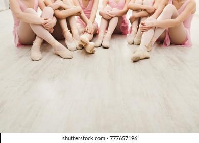 Little ballerinas talking in ballet studio. Group of girls having break in practice, sitting on floor, crop. Classical dance school