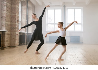 Little ballering girl dancing together with her trainer during classes in dance studio