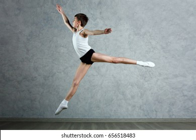 Little ballet caucasian boy dancer jump in a studio in white shirt and black underpants ballet uniform. Full-lenght portrait.