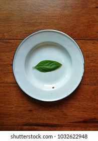 The little basil leaf on the white dish and all on the wood background. The basil is a herbal plant good for health.