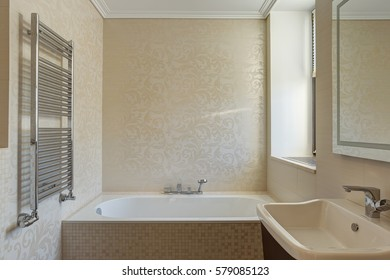Little bathroom in beige and white colors, with ceramic bath under window and in corner. Big mirror on wall and  beige sink near. Lighting bathroom.