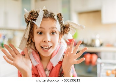 Little beautiful amazed girl with hair curlers on her head and pink bathrobe on background of kitchen.