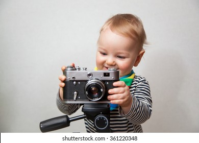 Little beautiful baby boy with smiley face holding vintage film photocamera on a light gray wall background