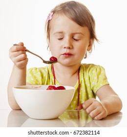 A little beautiful baby girl eating and enjoying of fresh strawberries. (Health, Nutrition, Vitamins, Happy Childhood Concept)