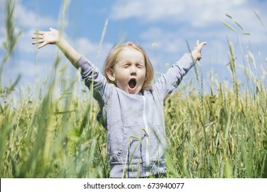 Little beautiful baby girl outdoors in a field in the fresh air happy