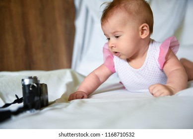 Little beautiful baby girl wondering looks at vintage film photo camera on a wooden wall background