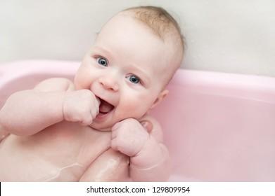 Little beautiful blue-eyed baby taking a bath