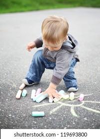 little beautiful boy draws with chalk on asphalt