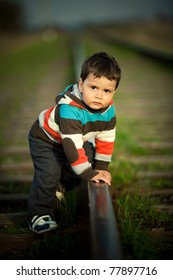 little beautiful boy plays on railroad
