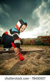 little beautiful boy plays in sandbox