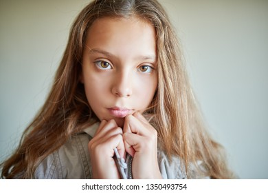 Little beautiful calm girl with long hair in gray jacket.
