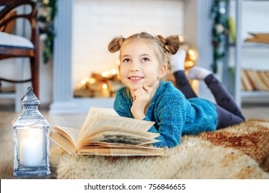 A little beautiful child reads a fairy tale in a book. Concept New Year, Merry Christmas, holiday, vacation, winter, childhood.