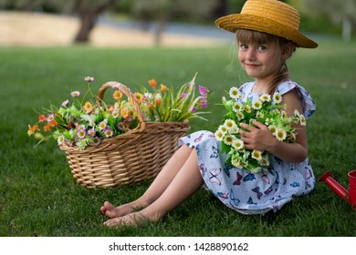 little beautiful girl of 4 years old in a dress and a hat with a bouquet of flowers in the park in the summer smiling in the garden