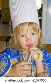 Little beautiful girl in blue dress and cook hat drinking water in stow.