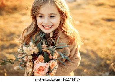 Little beautiful girl with a bouquet of flowers stands in the mountains in autumn