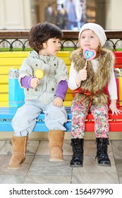 Little beautiful girl and boy with lollipops sit on bench in large store.