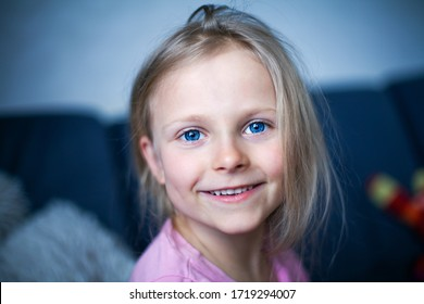Little beautiful girl with bright blue eyes smiles and looks at the camera. Happy child 6-7 years old. Head close up