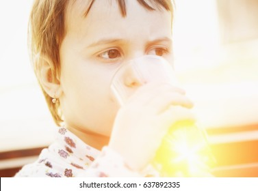 Little beautiful girl child drinks orange. (Vitamins, health, thirst, happy childhood concept)