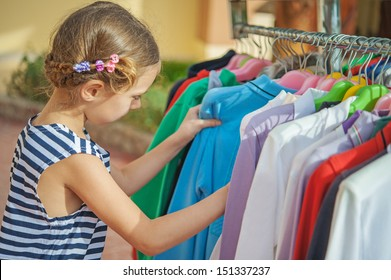 Little beautiful girl choose right clothes at store.