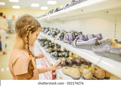 Little beautiful girl chooses shoes at a store.
