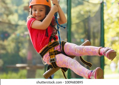 Little beautiful girl climbs on rope harness in summer city park.