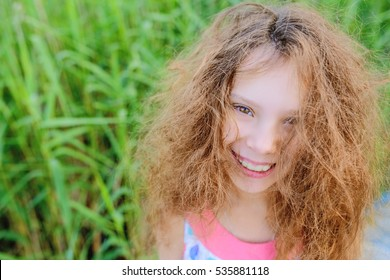 Little beautiful girl with curly hair close-up on a background of green garden.