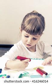 Little beautiful girl draws pencils and felt-tip pens