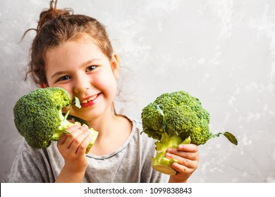 Little beautiful girl eating broccoli. Healthy vegan baby foods concept.
