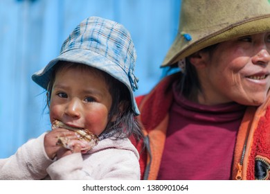 Little beautiful girl eating with her mom. January 2018. Cusco, Peru.