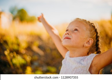 A little beautiful girl is happy with her arms raised