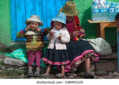 Little beautiful girl with her mom and her brothers eating. January 2018. Cusco, Peru.