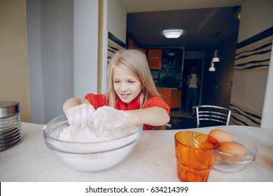 Little beautiful girl at home in the kitchen prepares to eat